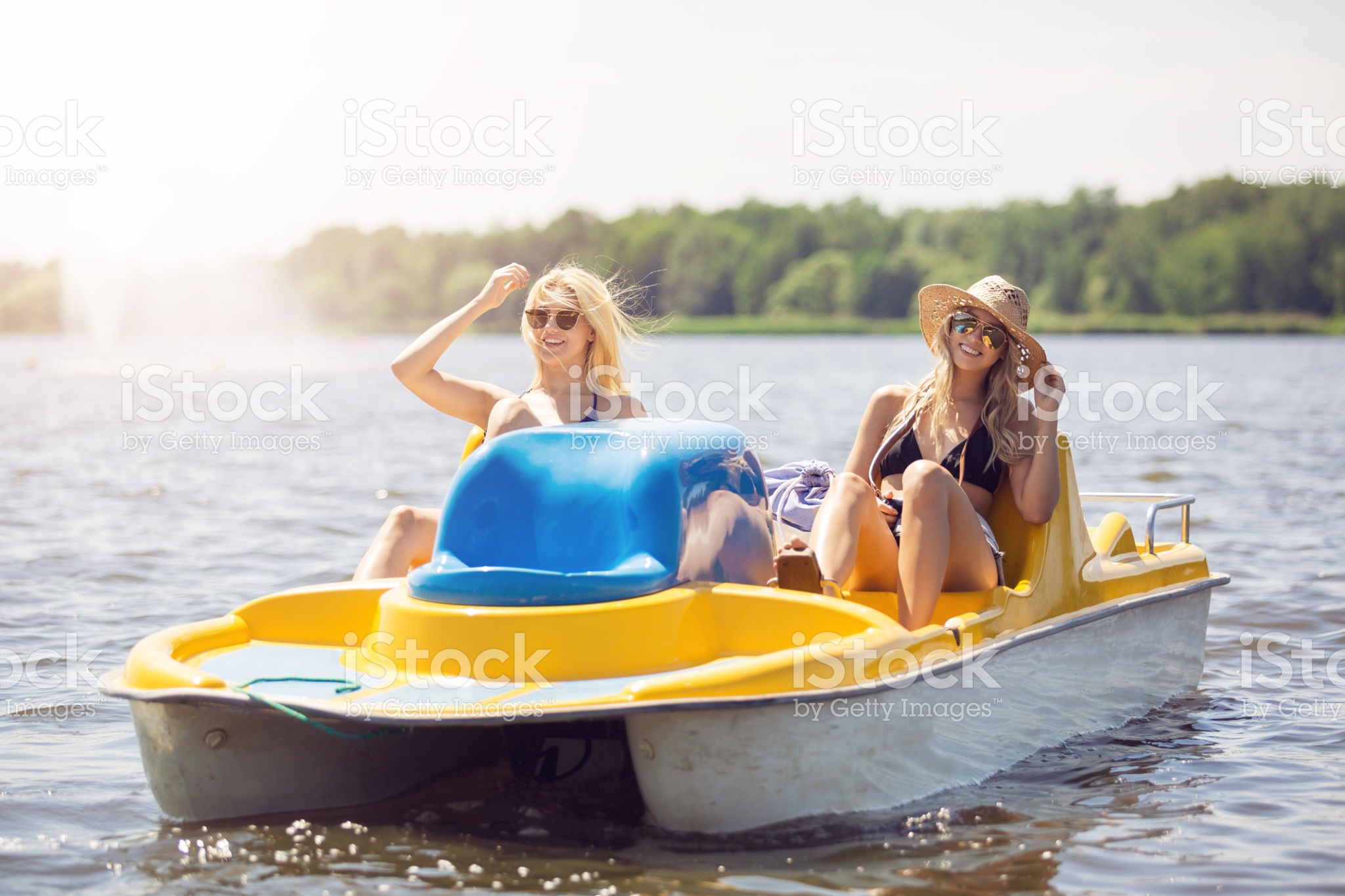 A photo of two happy women spending their holiday at the lake and swimming paddle boat.